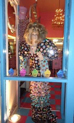 In the front window of Philly Cupcake stands this mannequin dressed in a cupcake decorated outfit.