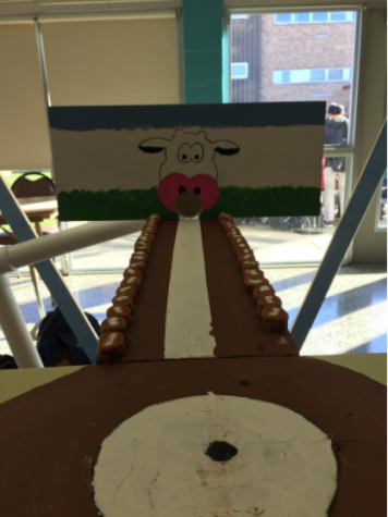 At the freshman booth,students roll a small pool ball down a runway and try to get the ball into the cow's mouth.